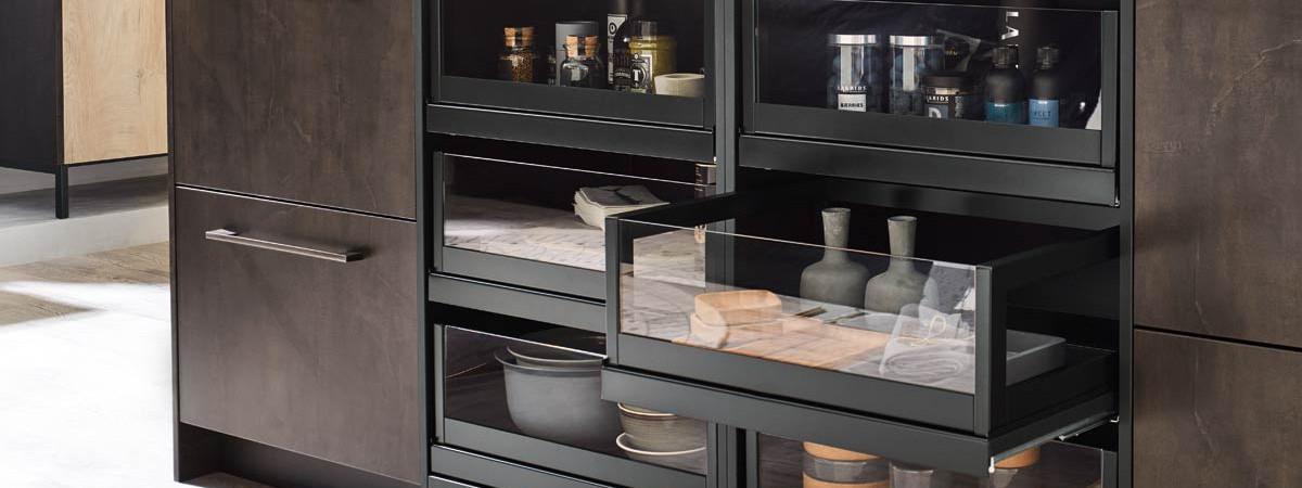 Een Keukenstudio van Vliet huisselectie keuken. Dit keukenblok is zwart en houtkleurig uitvoerd en heeft glazen panelen in de lades.