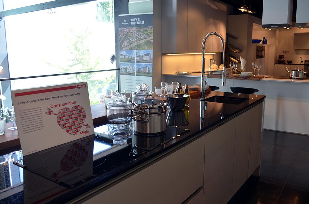 Een wit keukenblok met glanzend zwart keukenblad in de showroom van Keukenstudio van Vliet.