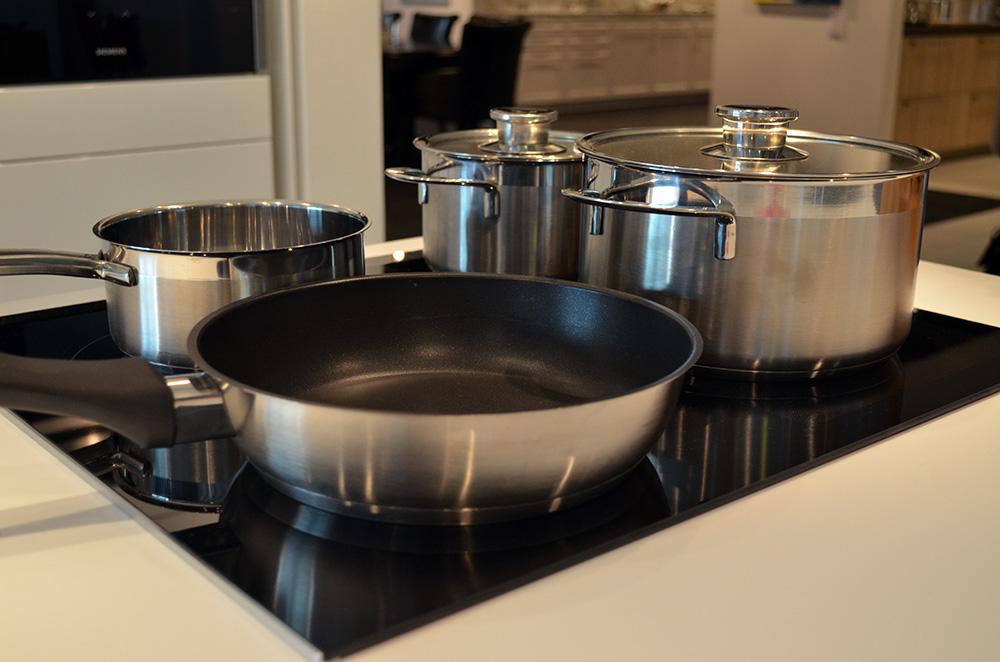 Een set pannen op een kookplaat in de showroom van Keukenstudio van Vliet.