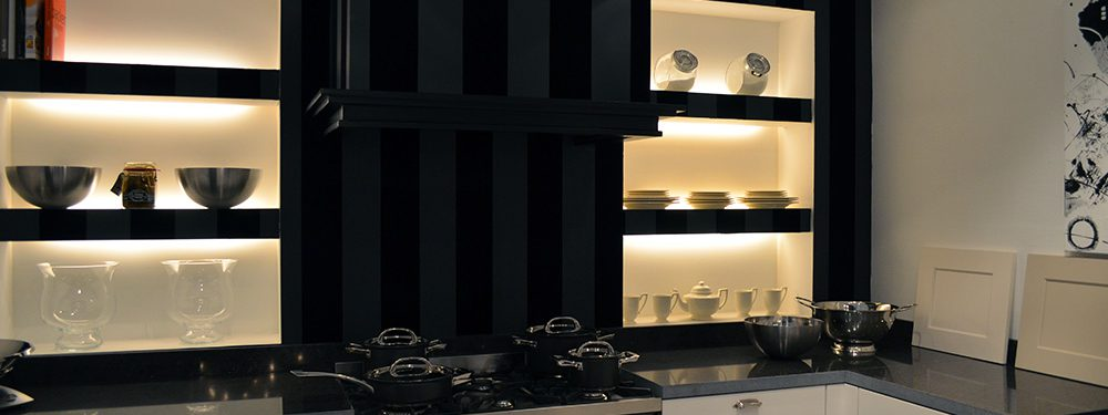 Een volledige keuken in de showroom van Keukenstudio van Vliet. Het witte keukenblok is gecombineerd met zwarte open bovenkasten.
