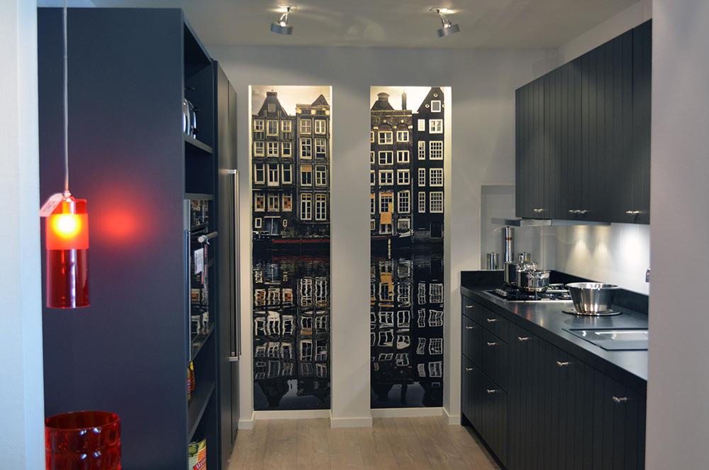 Een zwarte keuken in de showroom van Keukenstudio van Vliet. De keuken heeft vier bovenkastjes en vijf onderkasten.