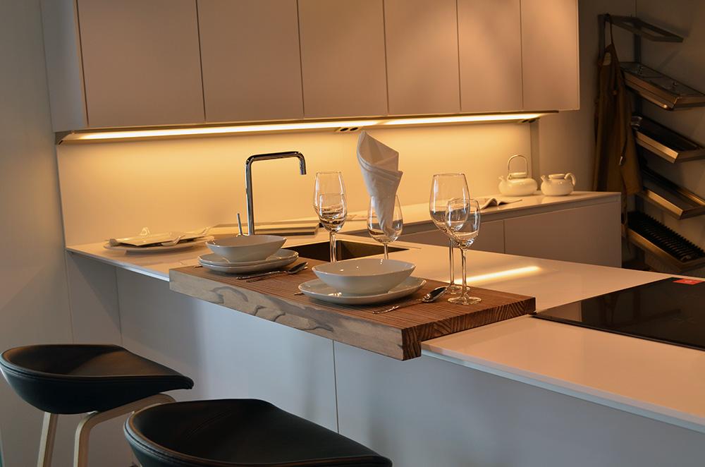 Een gedekte bar die tegen de keuken aan zit. De bar is wit uitgevoerd.