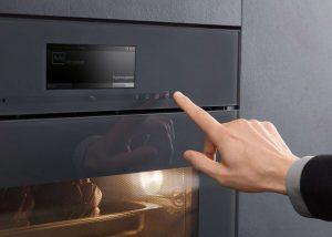De Artline inbouwappraten van Miele. Een hand raakt het touchpaneel aan om de oven te openen.