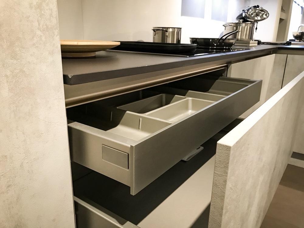 De betonlook keuken van Keukenstudio van Vliet. Deze hoekkeuken heeft uitschuifbare bestekbakken in de lade.