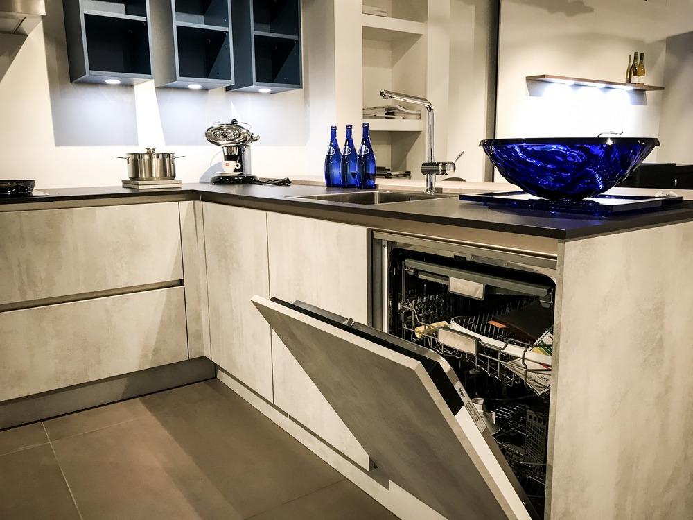 Een Keukenstudio van Vliet huisselectie keuken met betonlook. Dit hoekkeuken model heeft een volledig geïntegeerde vaatwasser.