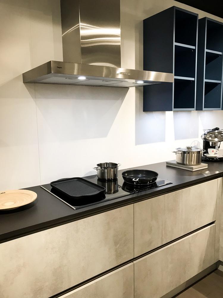 Een betonlook keuken uit de huisselectie van Keukenstudio van Vliet. Dit keukenblok heeft een ingebouwde kookplaat in het zwarte werkblad. Boven de kookplaat hangt een RVS afzuigkap.