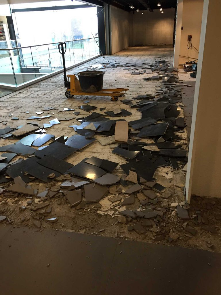 De oude tegels worden verwijderd uit de showroom.