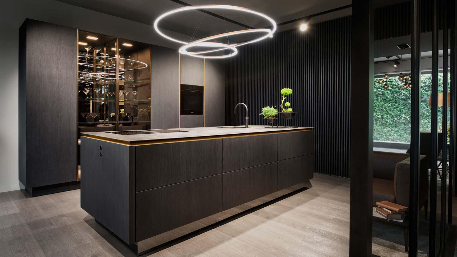 Een open SieMatic Pure keuken met spiraal verlichting. Het vrijstaande keukenblok is zwart uitgevoerd.