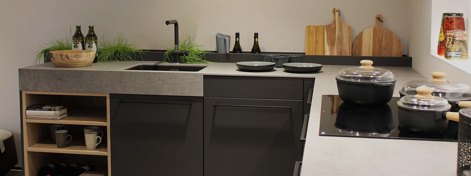 Een zwart grijze Siematic hoekkeuken met ingebouwde kookplaat en gootsteen.