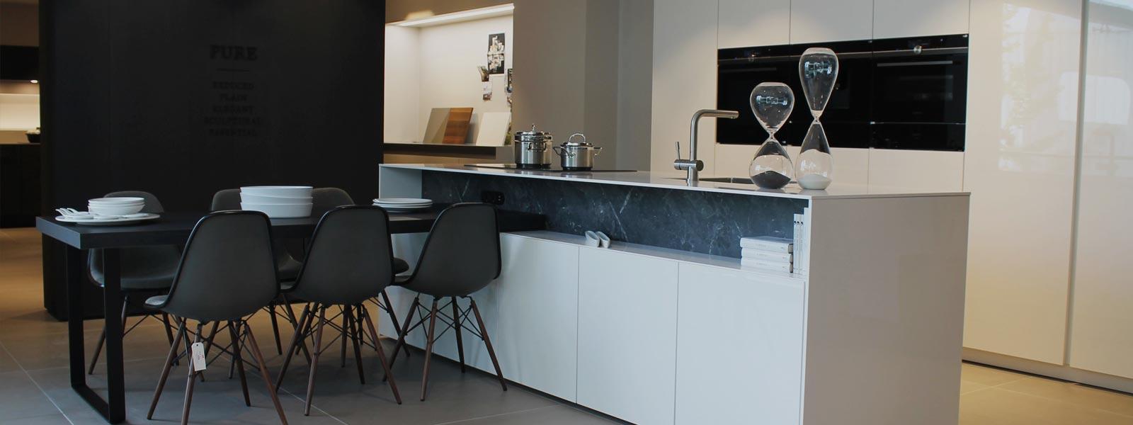 Wit keukenblok in de showroom van Keukenstudio van Vliet. Een zwarte tafel met zwarte stoelen die gedekt is met wit servies.