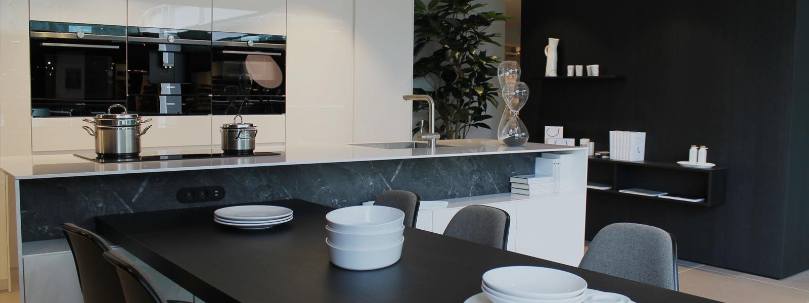 Een zwarte tafel met wit servies er op geplaatst in de showroom van Keukenstudio van Vliet. Een overwegend wit keukenblok met pannen op de kookplaat.