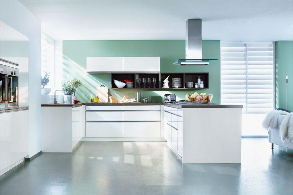 Een huisselectie keuken van Keukenstudio van Vliet. De wit uitgevoerde keuken heeft een donker werkblad. De afzuigkap is omringd door een glazen plaat.