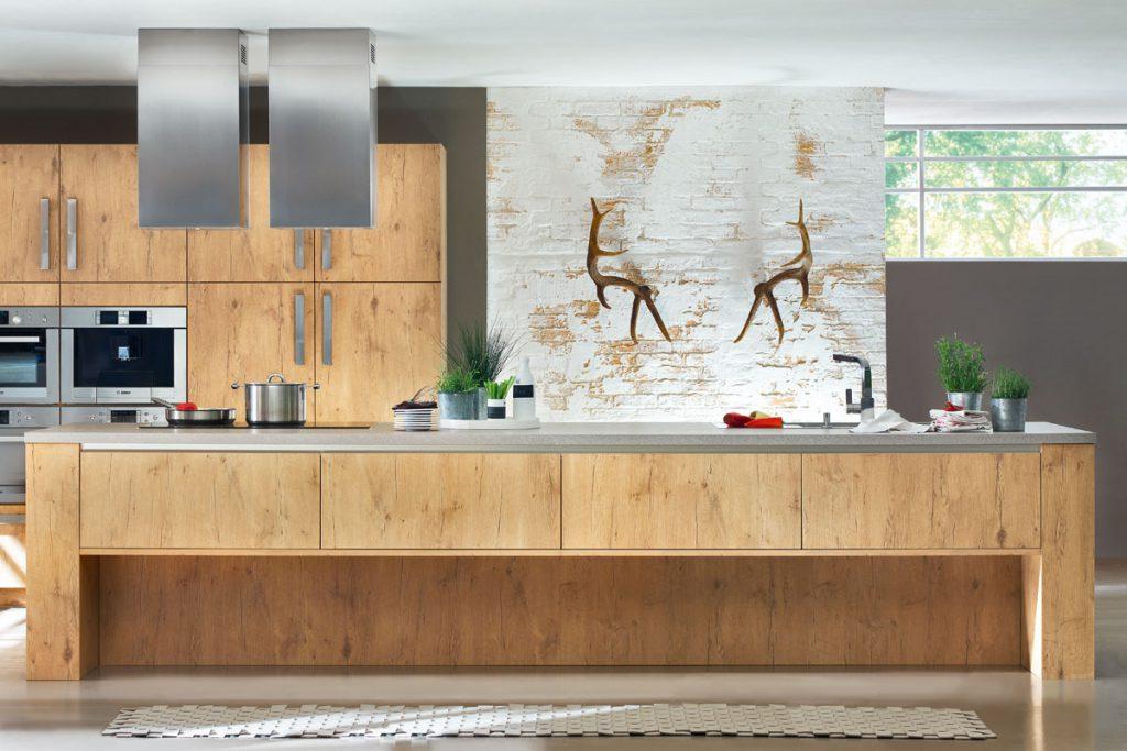 Een in houtkleur uitgevoerde huisselectie keuken van Keukenstudio van Vliet. Deze keuken bevat een vrijstaand groot keukenblok en een wandgedeelte met ingebouwde oven. Het keukenblok heeft een grijs werkblad.