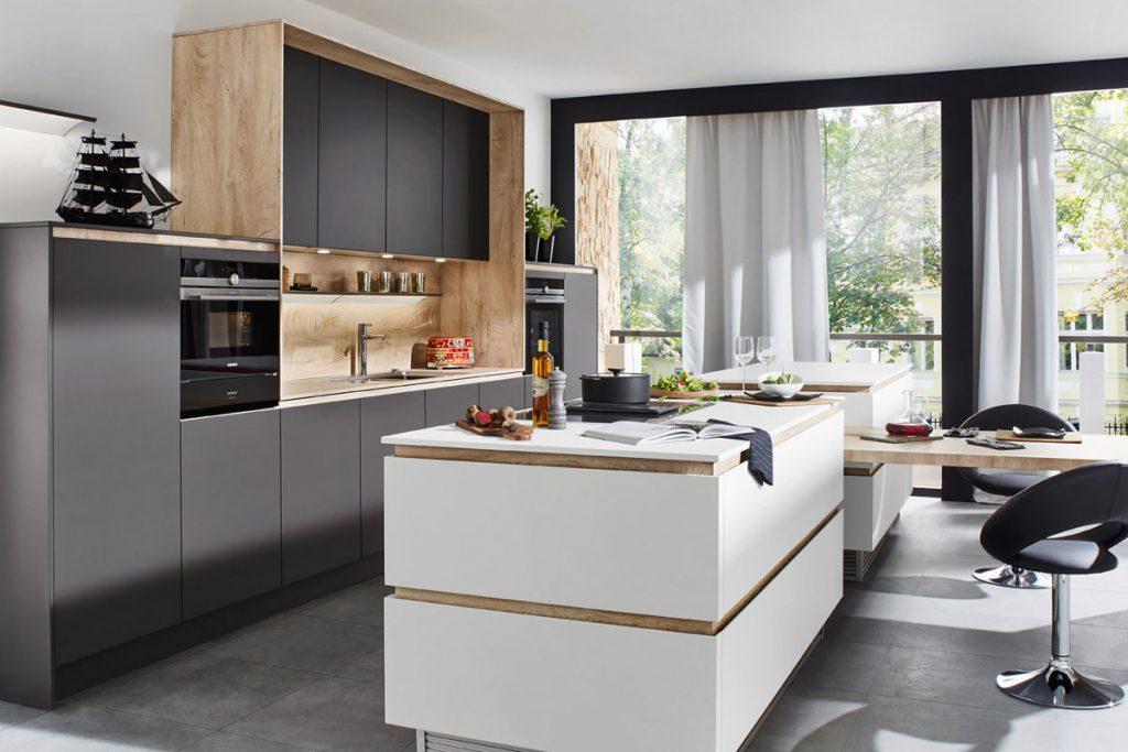 Een Keukenstudio van Vliet huisselectie keuken met een wit keukeneiland. Het wandgedeelte heeft zwarte panelen en een ombouw en achterwand van hout.