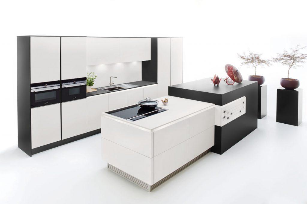 Een Keukenstudio van Vliet huisselectie keuken in zwart-wit uitgevoerd. De ombouw van het grote wand gedeelte is zwart en accentueert het witte van de panelen. De keuken bevat nog twee vrijstande eilanden die respectievelijke zwart en wit zijn.