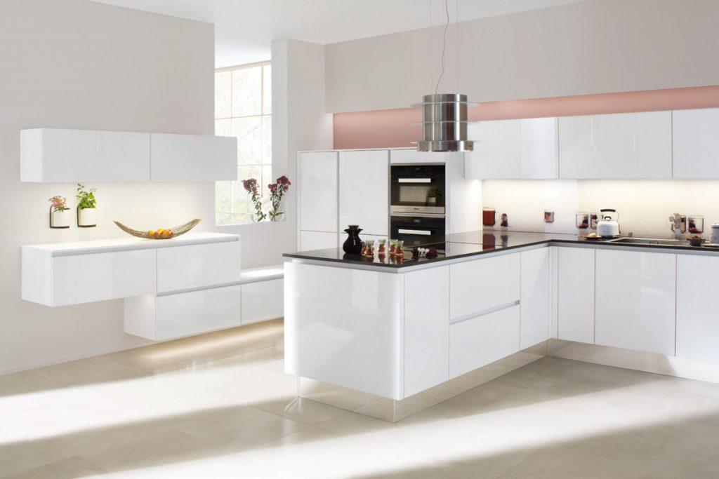 Een Keukenstudio van Vliet hoekkeuken met witte keukenkasten en zwarte keukenbladen. Deze keuken heeft een ingebouwde oven.