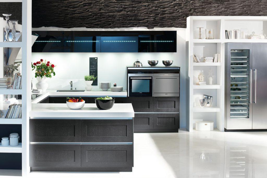 Een U vormige huisselectie keuken van Keukenstudio van Vliet. Deze keuken is voornamelijk zwart en wit van kleur. Het keukenblad is wit en de keukenkasten zijn zwart.