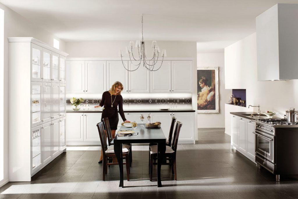 Een witte klassiek ogende keuken van Keukenstudio van Vliet. De keukenbladen zijn zwart gekleurd.