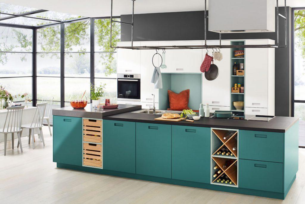 Een fris gekleurd keukenblok van Keukenstudio van Vliet. De gekleurde keukenkasten steken netjes af tegen het zwarte keukenblad en de witte grote keukenkasten.