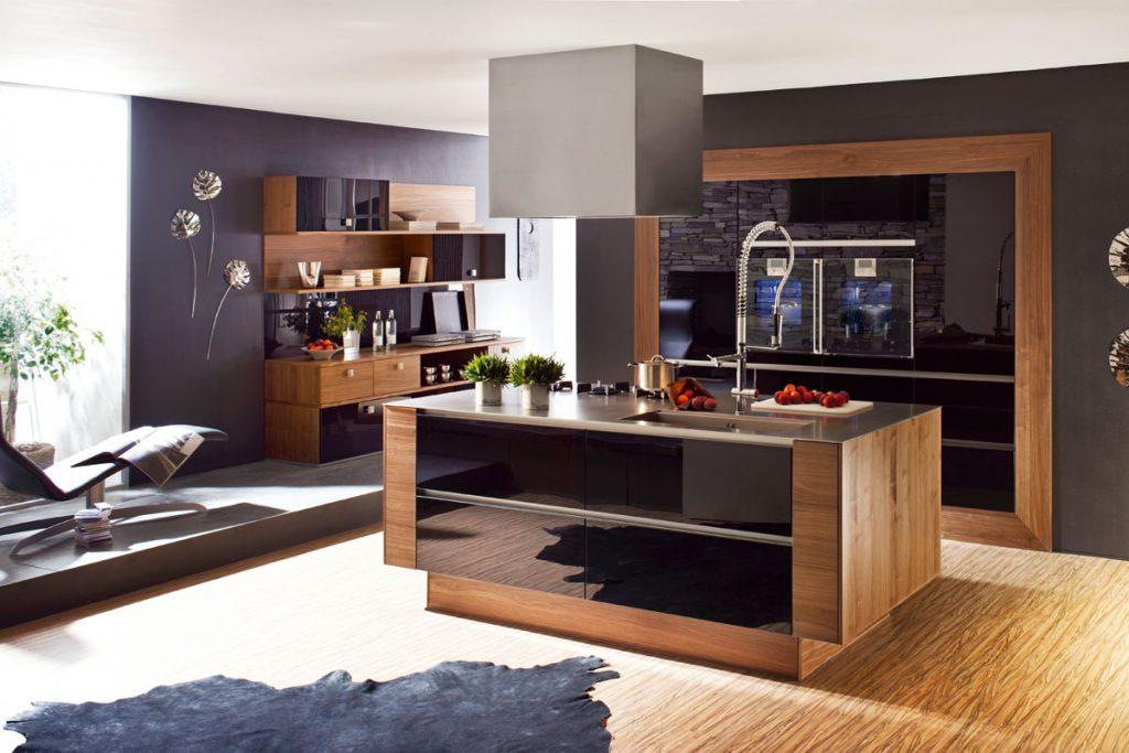 Een huisselectie keuken van Keukenstudio van Vliet. Deze keuken heeft een vrijstaand keukeneiland met houtkleurige ombouw. Het keukenblok is afgewerkt met zwarte panelen voor de keukenkastjes.