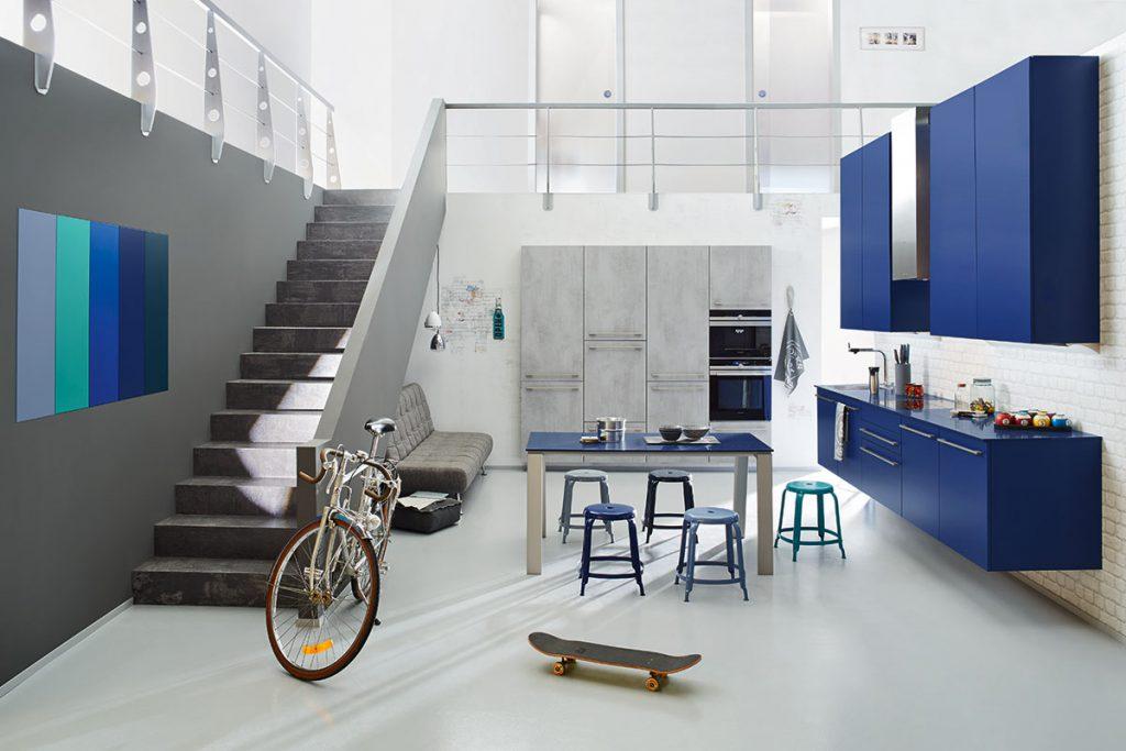 Een Keukenstudio van Vliet huisselectie keuken. De blauw uitgevoerde keukenkasten zijn hangend aan de muur bevestigd. Er is een bijpassend gekleurde tafel met krukjes.