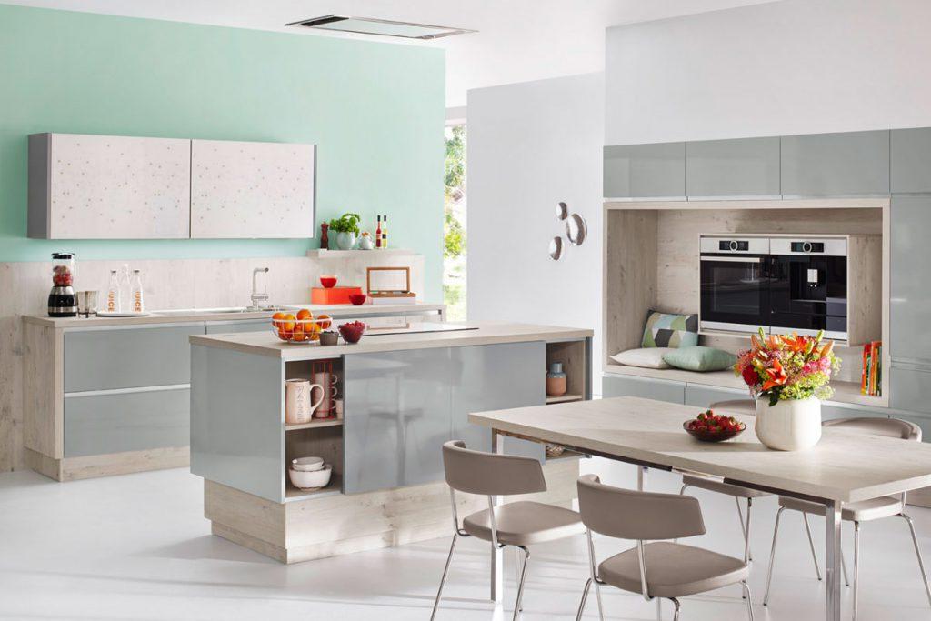 Een Keukenstudio van Vliet huisselectie keuken met grijstinten. De ombouw is in lichte houtkleur uitgevoerd en de panelen zijn grijs.