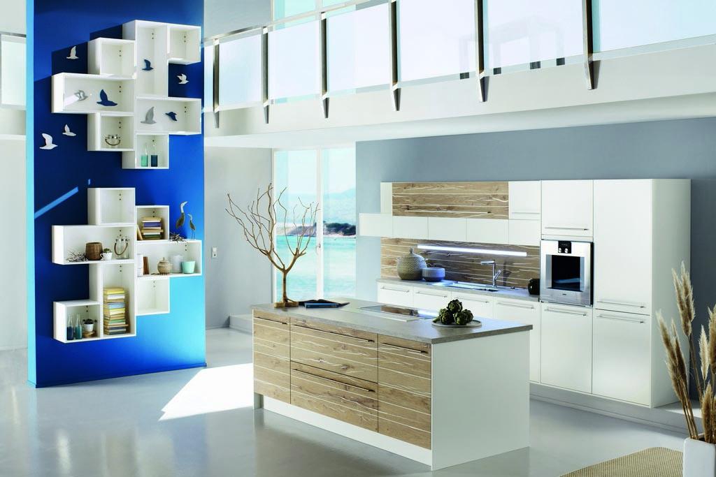 Keukenstudio van Vliet huisselectie witte keuken met vrijstaand kookeiland met ingebouwde kookplaat. Het keukenblok tegen de muur heeft een ingebouwde oven en spoelbak. Een aantal panelen zijn houtkleurig afgewerkt.