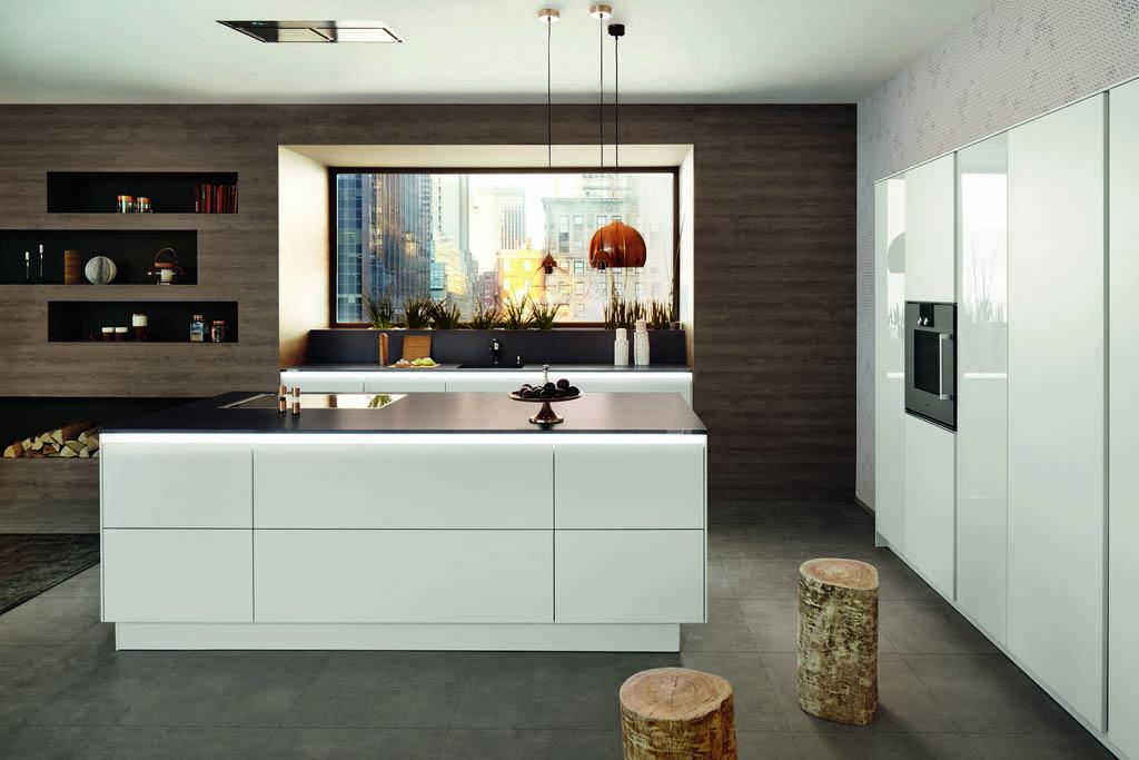 Een huisselectie wit-zwarte keuken van Keukenstudio van Vliet. De keukenkasten zijn wit met een zwart keukenblad er bovenop. Rechts staan witte hoge keukenkasten met een ingebouwde oven.