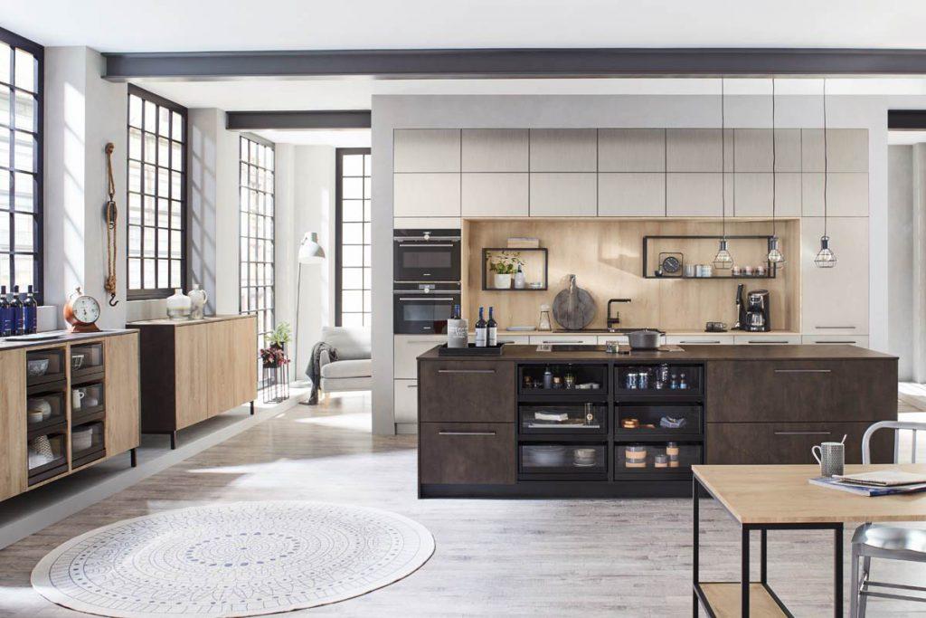 Een huisselectie Keukenstudio van Vliet keuken. Het vrijstaande gedeelte is houtkleurig met zwarte lades. De lades hebben glazen panelen.