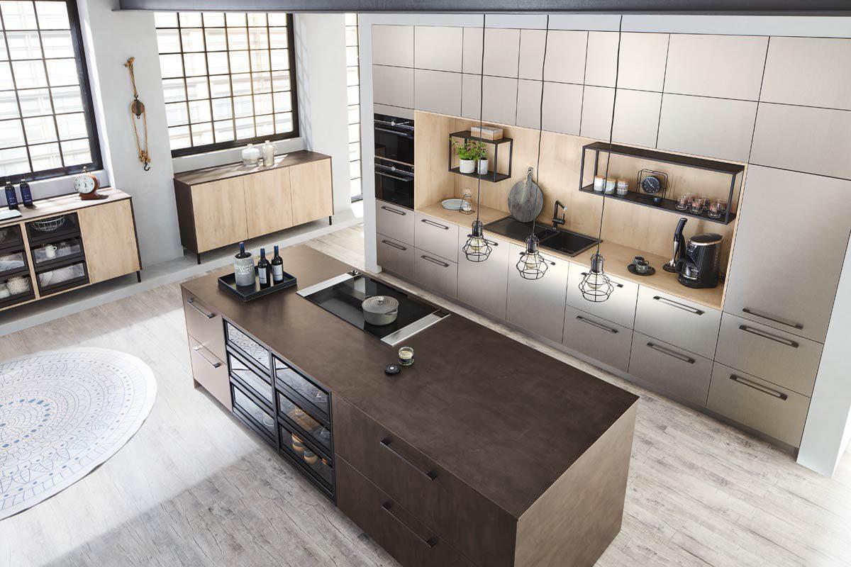 Een Keukenstudio van Vliet huisselectie keuken. Het vrijstaande keukenblok is zwart en houtkleurig met glazen panelen in de lades. Het wand gedeelte bestaat uit tien kleine keukenkastjes en twee grote keukenkasten.