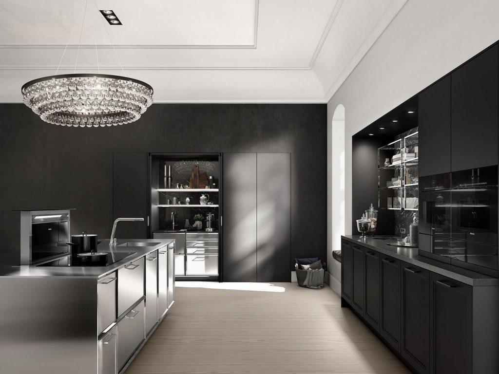 Een SieMatic Classic Beauxarts keuken uitgevoerd in het mat zwart. De keukenkastjes van het kookeiland hebben brede chroom gekleurde handgrepen. De grote zwarte kast is greeploos.