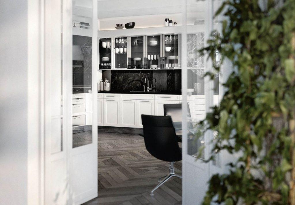 Een witte keuken van SieMatic Classic Beauxarts. Het onderste keukenblok is afgewerkt met brede handgrepen. De bovenkasten zijn uitgevoerd met glazen deurtjes met een chroom gekleurde omlijsting. Deze keuken heeft een zwart marmer kleurige keukenachterwand.