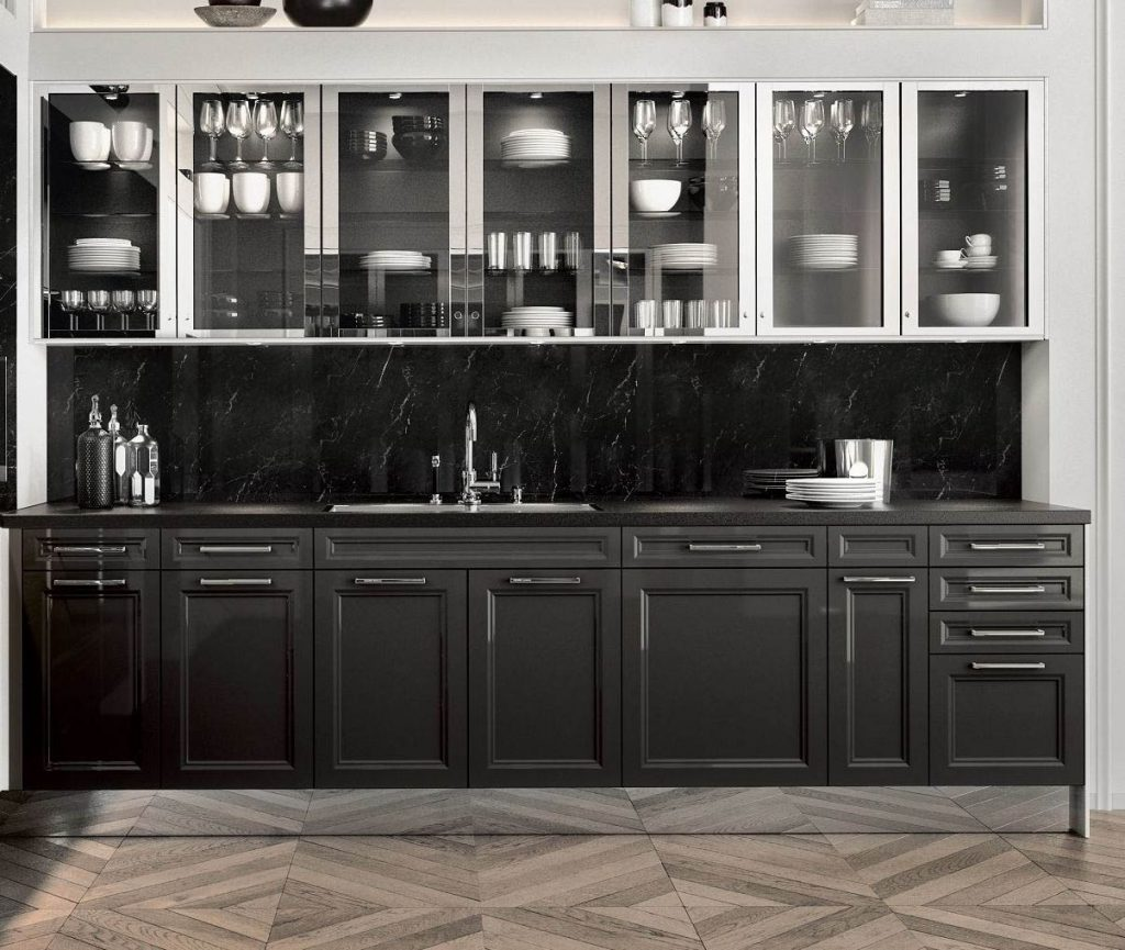 Een zwarte keuken van SieMatic Classic Beauxarts. Het onderste keukenblok is afgewerkt met brede handgrepen. De bovenkasten zijn uitgevoerd met glazen deurtjes met een chroom gekleurde omlijsting. Deze keuken heeft een zwart marmer kleurige keukenachterwand.