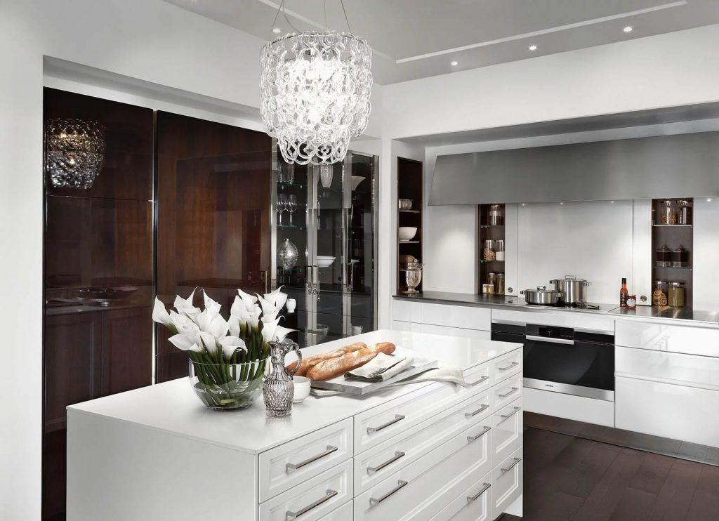 Een SieMatic Classic Beauxarts keuken met ingebouwde oven en kookplaat. Het keukeneiland in het midden heeft een minder glanzende afwerking dan het keukenblok en heeft wel zichtbare handgrepen.