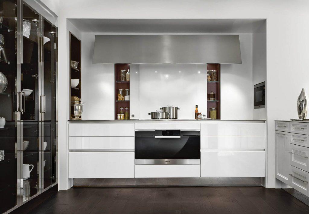 Een keuken van SieMatic Classic Beauxarts met een ingebouwde oven en kookplaat. Het witte keukenblok heeft geen grepen die in het zicht zitten.
