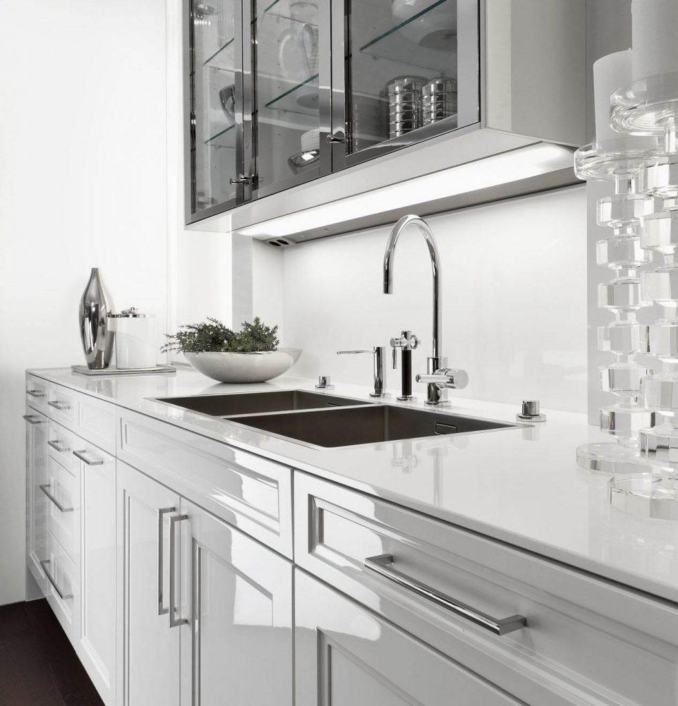 Een glanzend witte keuken van SieMatic Classic Beauxarts. De keukenkastjes en het werkblad zijn beide glanzend wit. De bovenkasten hebben glazen deuren met een chroom gekleurde omlijsting.