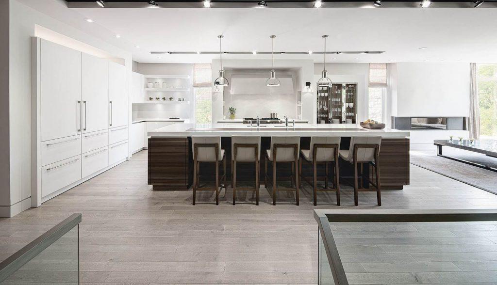 SieMatic Classic keuken met vrijstaand keukeneiland. Het eiland heeft een houtkleurige ombouw en een wit werkblad. De keuken is verder volledig in het wit uitgevoerd.