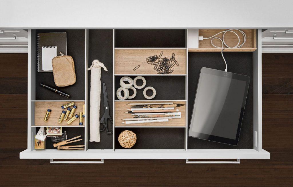 SieMatic Aluminium interieursysteem voor in de lade, waarin een tablet, potloden, plakband, en batterijen liggen opgeborgen.