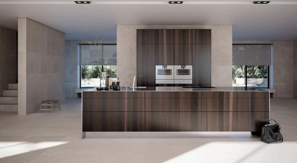 SieMatic Pure keukenblok met ingebouwde kookplaat en spoelbak. De keukenkasten zijn van eikenhout (smoked oak) en het werkblad is glanzend zwart.. Er achter een hoge keukenkast met twee ingebouwde ovens in hetzelfde eikenhout als het keukenblok.
