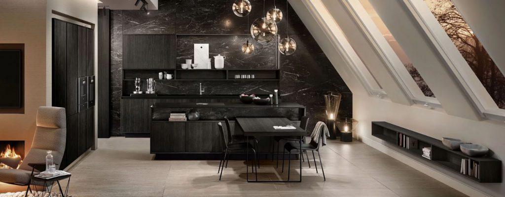 SieMatic Pure mat zwarte keuken met vrijstaand keukeneiland. De hoge keukenkasten hebben twee ingebouwde ovens. De werkbladen zijn glanzend zwart.