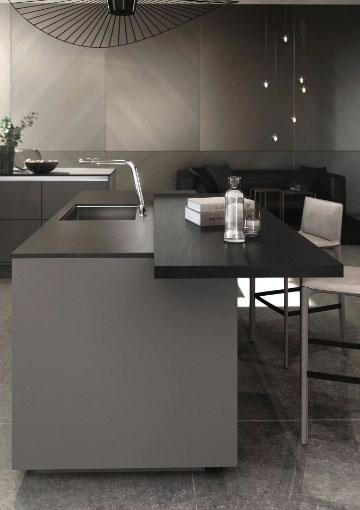 SieMatic Pure keukenblok met geïnstalleerde spoelbak. Er staat een zwarte aanzettafel tegen het keukenblok aan.