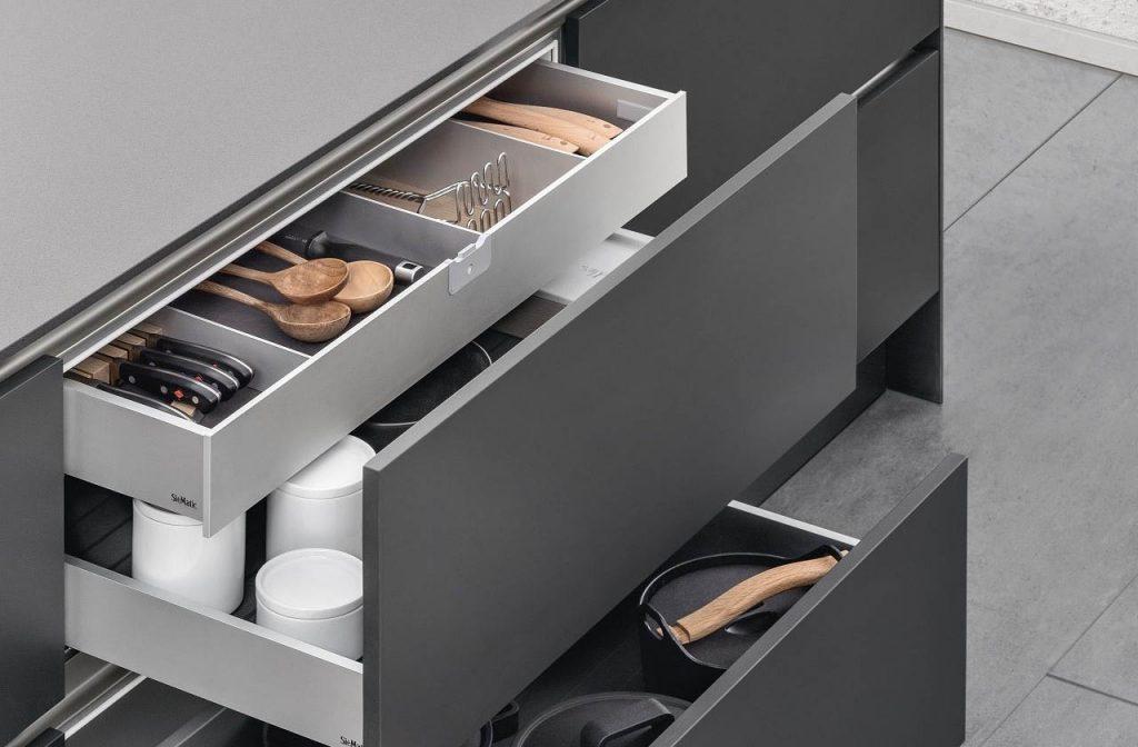 SieMatic Aluminium interieursysteem met grote en kleine lades. De grote laden bevatten pannen en de kleinere laden bevatten containers voor voedsel of keukengerei.