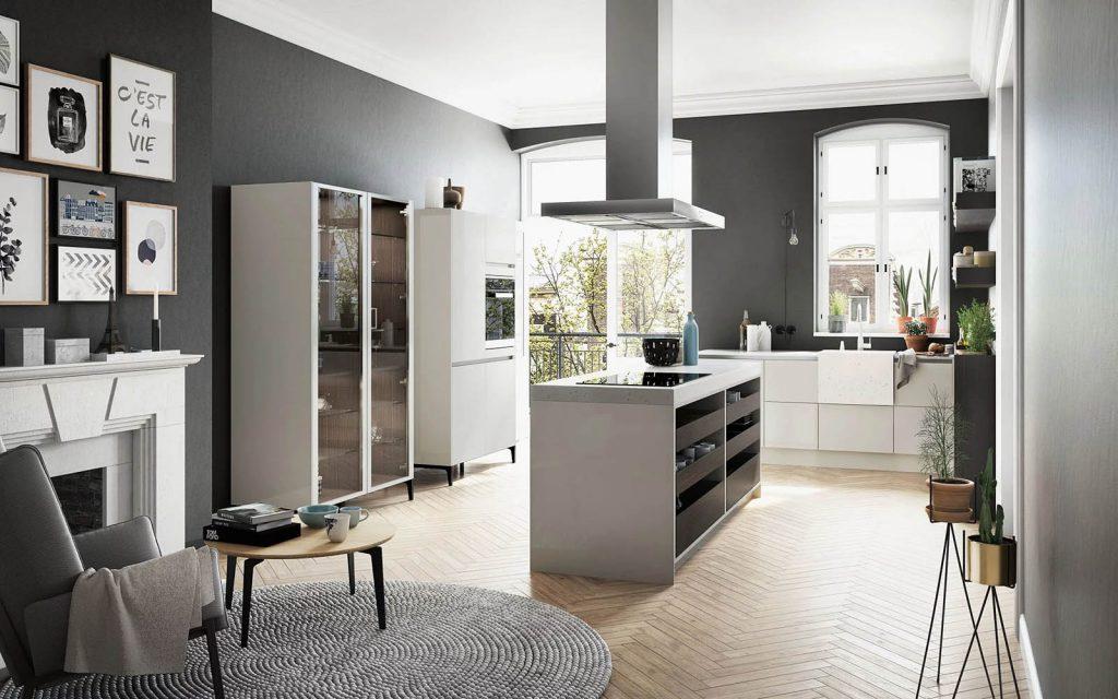 Een SieMatic Urban keuken met kookeiland. Het kookeiland heeft een witte ombouw met daarin zes donkere laden en een ingebouwde kookplaat. Het keukenblok met spoelbak is compleet in het wit uitgevoerd.