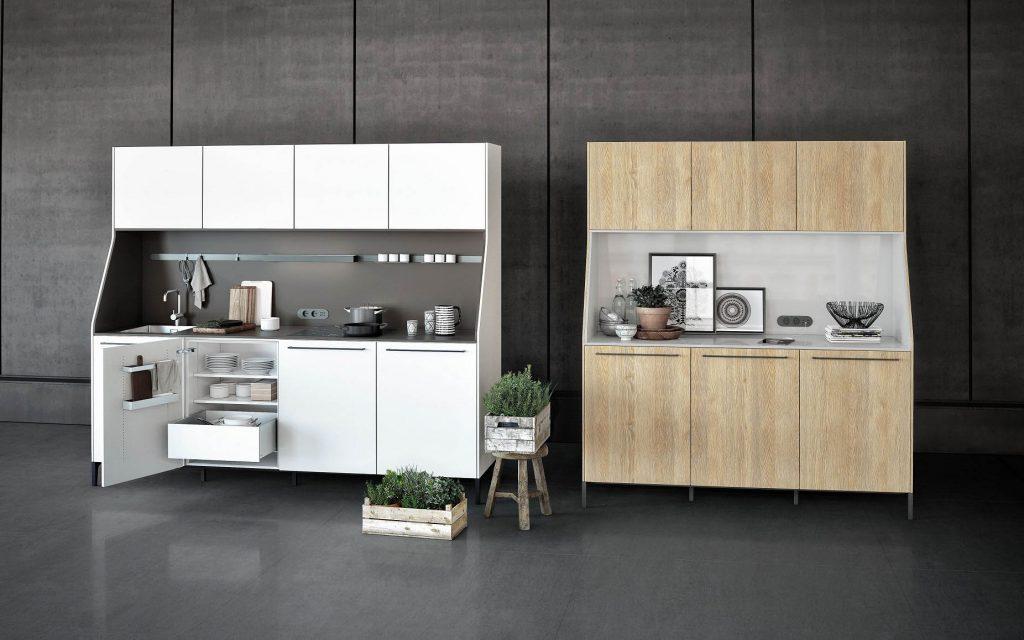 SieMatic Urban keukenblokken. De het linkse keukenblok is wit met een donkerbruin werkblad en achterwand. Het rechtse keukenblok heeft een lichte houtskleur met een grijs werkblad en achterwand.