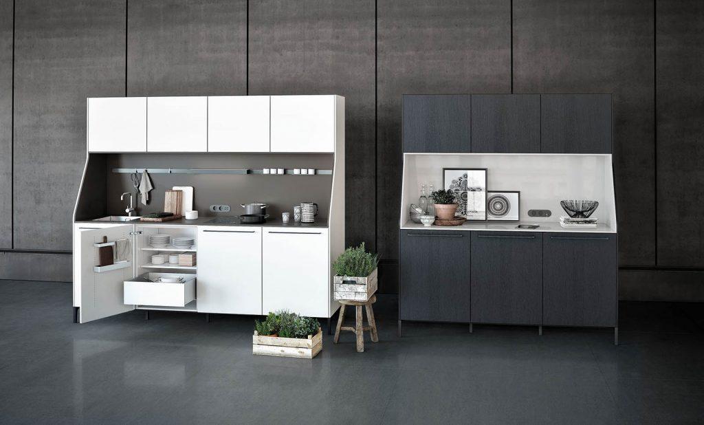 SieMatic Urban keukenblokken. De het linkse keukenblok is wit met een donkerbruin werkblad en achterwand. Het rechtse keukenblok is mat zwart met een wit werkblad en achterwand.