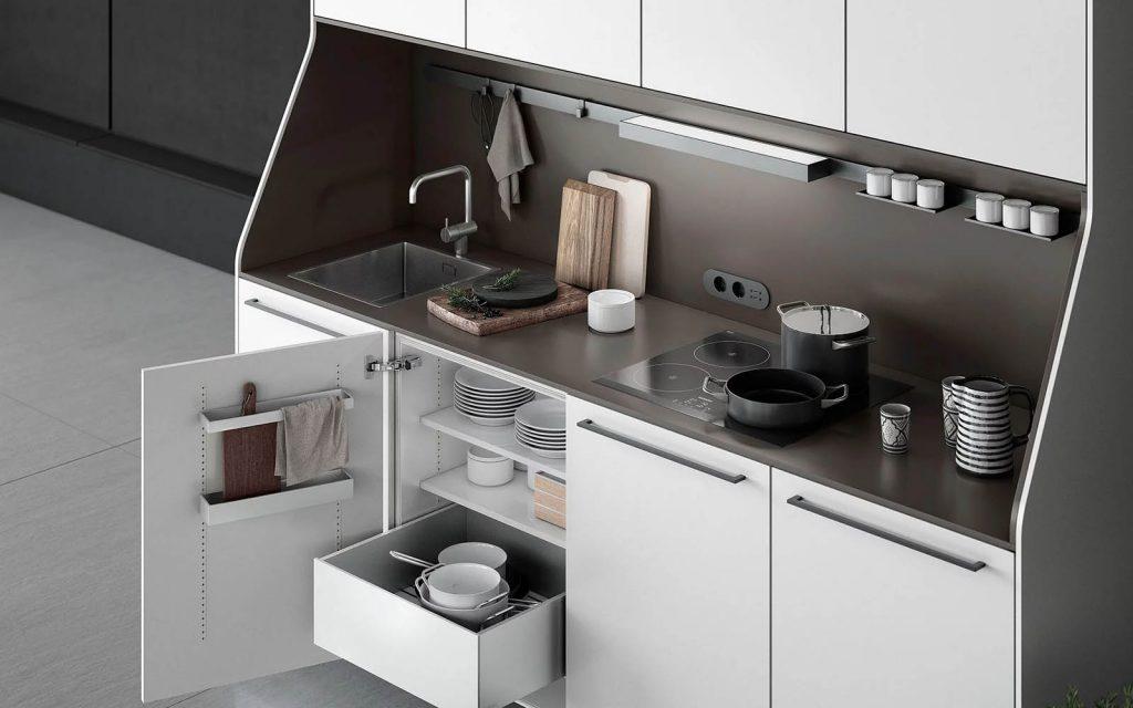 SieMatic Urban keukenblok. De keukenkasten hebben witte panelen en het blok heeft een donkerbruin werkblad met ingebouwde spoelbak en kookplaat.
