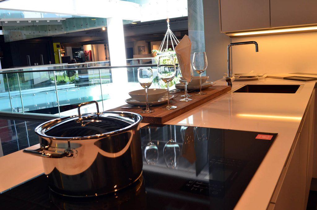 Een wit keukenblok met geïnstalleerde kookplaat. Het keukenblok fungeert ook als klein barretje.